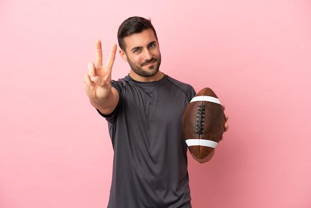 Jovem homem caucasiano jogando rugby isolado em um fundo rosa sorrindo e mostrando sinal de vitória