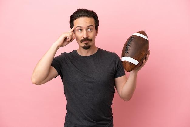 Jovem homem caucasiano jogando rugby isolado em um fundo rosa, tendo dúvidas e pensando