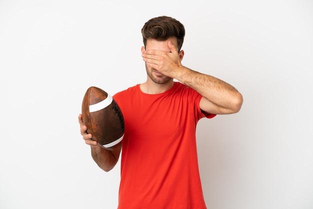 Jovem homem caucasiano jogando rugby, isolado no fundo branco, cobrindo os olhos com as mãos. não quero ver nada