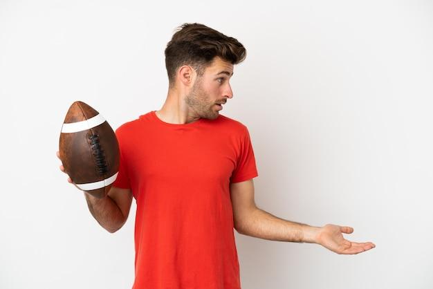 Jovem homem caucasiano jogando rugby isolado no fundo branco com expressão de surpresa enquanto olha para o lado