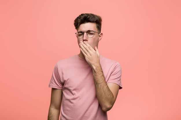 Jovem homem caucasiano legal bocejando mostrando um gesto cansado, cobrindo a boca com a mão