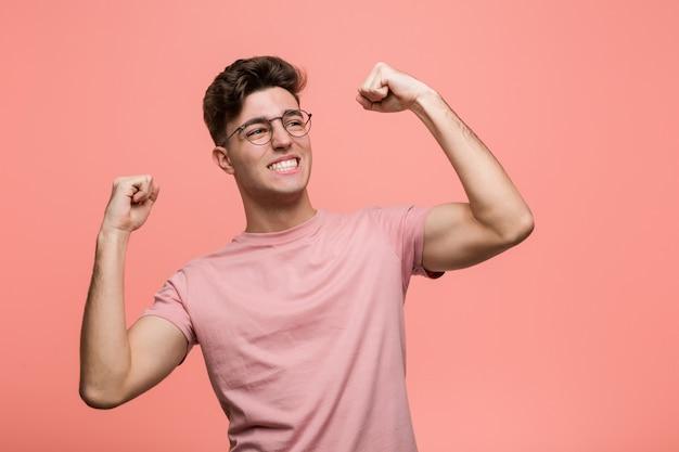 Jovem homem caucasiano legal, levantando o punho após uma vitória, vencedor.