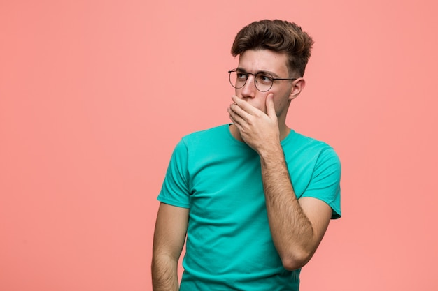 Jovem homem caucasiano legal pensativo olhando para uma cópia cobrindo a boca com a mão.