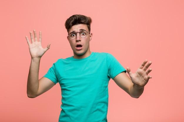 Jovem homem caucasiano legal sendo chocado devido a um perigo iminente