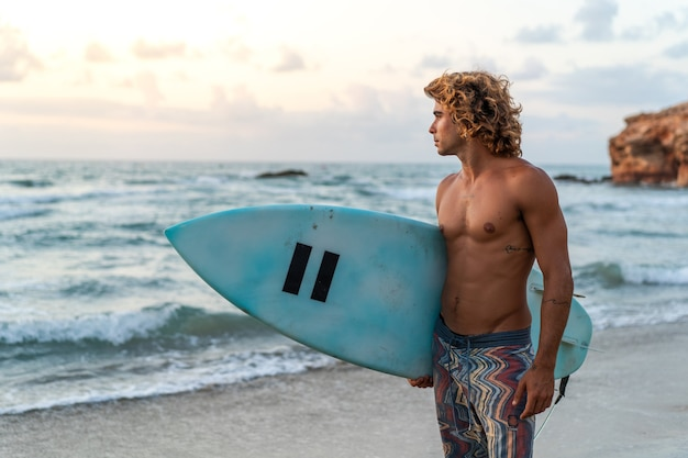 Jovem homem caucasiano levanta cedo para fazer surf