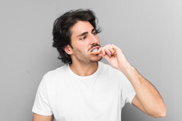 Jovem homem caucasiano limpando os dentes com uma escova de dentes isolada em uma parede cinza