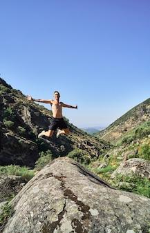 Jovem homem caucasiano, livre e feliz, pulando de braços abertos em uma bela paisagem com montanhas.