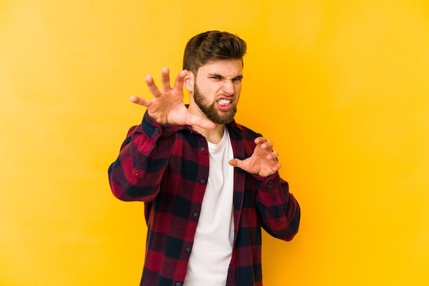 Jovem homem caucasiano mostrando garras imitando um gato, gesto agressivo.