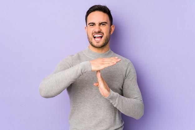 Jovem homem caucasiano, mostrando um gesto de tempo limite.