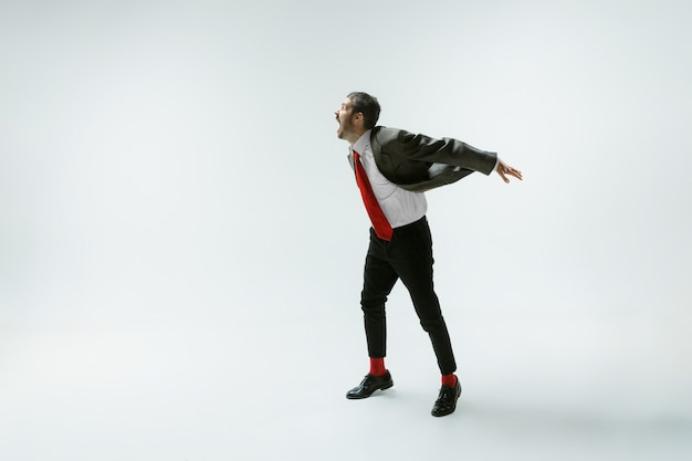 Jovem homem caucasiano movendo-se com flexibilidade na parede branca