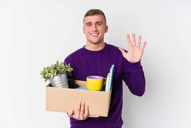 Jovem homem caucasiano, movendo-se para uma nova casa sorrindo alegre mostrando o número cinco com os dedos.