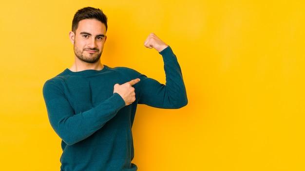 Jovem homem caucasiano na parede amarela, mostrando o gesto de força com os braços