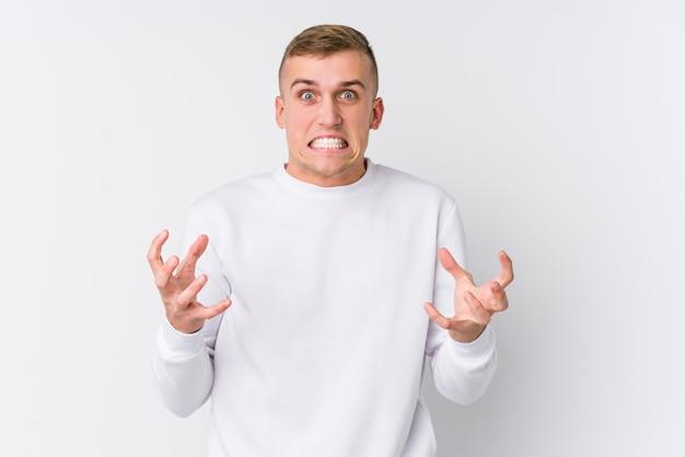 Jovem homem caucasiano na parede branca chateado gritando com mãos tensas.