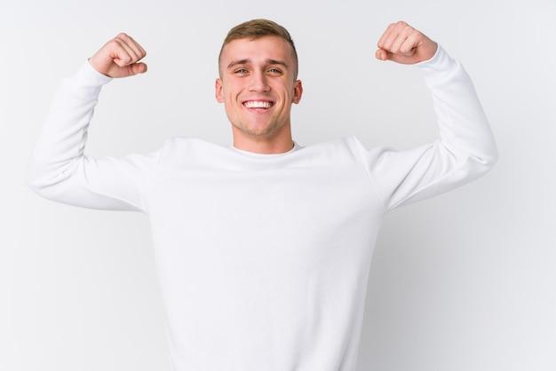 Jovem homem caucasiano na parede branca, mostrando o gesto de força com os braços, símbolo do poder feminino