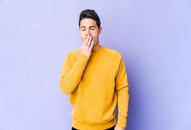 Jovem homem caucasiano na parede roxa bocejando, mostrando um gesto cansado, cobrindo a boca com a mão.