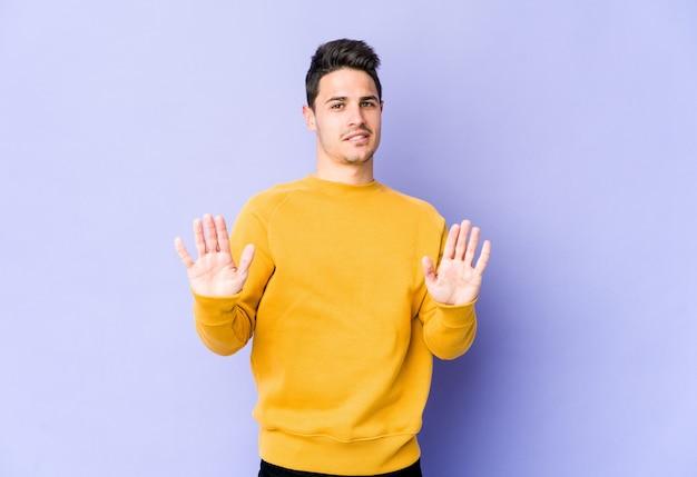 Jovem homem caucasiano na parede roxa rejeitando alguém mostrando um gesto de nojo.