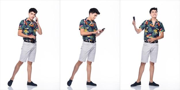Jovem homem caucasiano no verão tropical impresso camisa polo preta curta e andar no sorriso feliz ação com o uso de telefone celular inteligente, fundo branco isolado, conceito de grupo de colagem de corpo inteiro