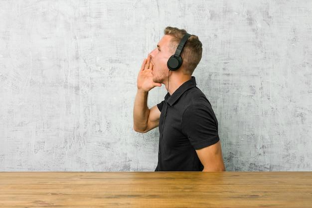 Jovem homem caucasiano ouvindo música com fones de ouvido, gritando e segurando a palma da mão perto da boca aberta.