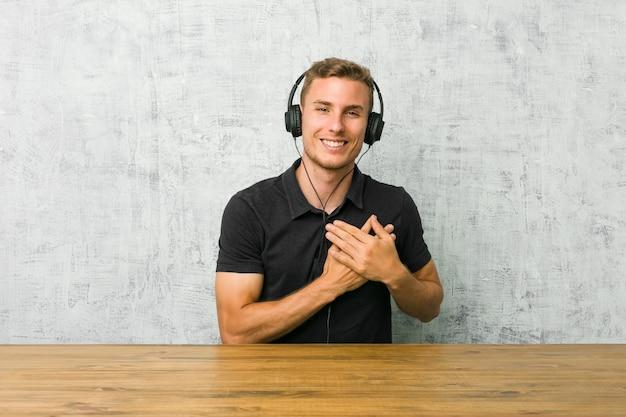 Jovem homem caucasiano ouvindo música com fones de ouvido tem uma expressão amigável, pressionando a palma da mão no peito. conceito de amor.