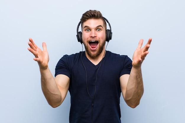 Jovem homem caucasiano ouvindo música, comemorando uma vitória ou sucesso