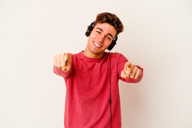 Jovem homem caucasiano ouvindo música isolada em uma parede branca com sorrisos alegres apontando para a frente