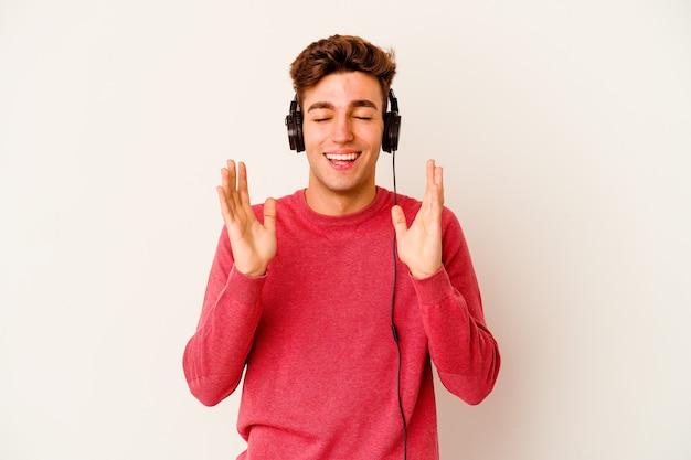 Jovem homem caucasiano ouvindo música isolada na parede branca alegre rindo muito