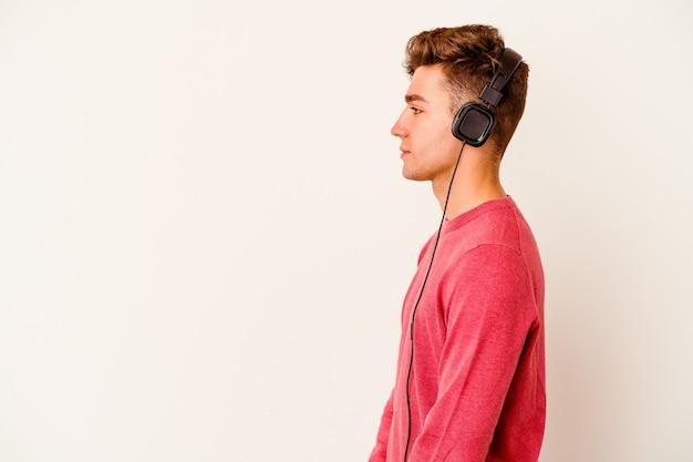 Jovem homem caucasiano ouvindo música isolada na parede branca, olhando para a esquerda, pose de lado.