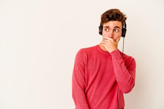 Jovem homem caucasiano ouvindo música isolada na parede branca pensativo, olhando para um espaço de cópia, cobrindo a boca com a mão.