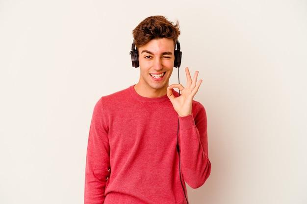 Jovem homem caucasiano ouvindo música isolada na parede branca pisca um olho e segura um gesto de ok com a mão.