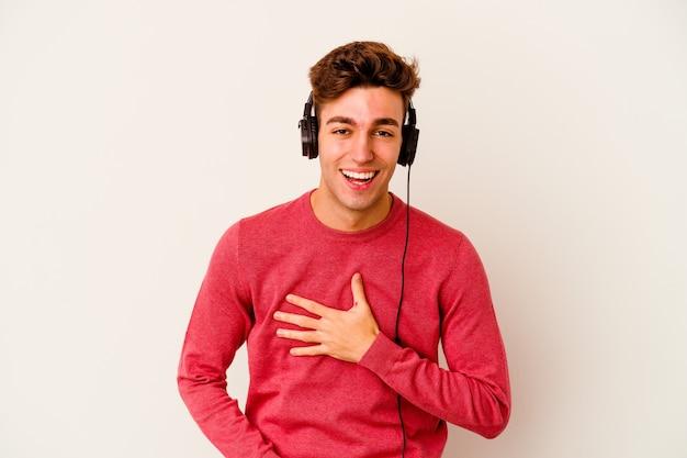 Jovem homem caucasiano, ouvindo música isolada na parede branca, ri alegremente e se diverte mantendo as mãos na barriga.
