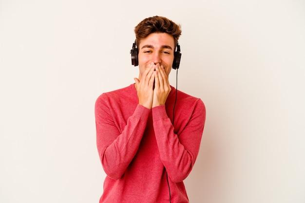 Jovem homem caucasiano ouvindo música isolada na parede branca, rindo de alguma coisa, cobrindo a boca com as mãos