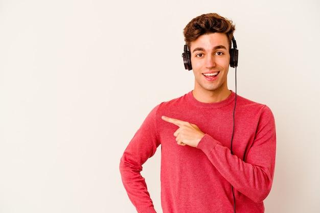 Jovem homem caucasiano ouvindo música isolada na parede branca, sorrindo e apontando de lado, mostrando algo no espaço em branco.