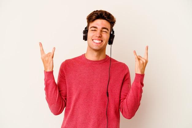 Jovem homem caucasiano ouvindo música isolada no fundo branco, mostrando um gesto de pedra com os dedos