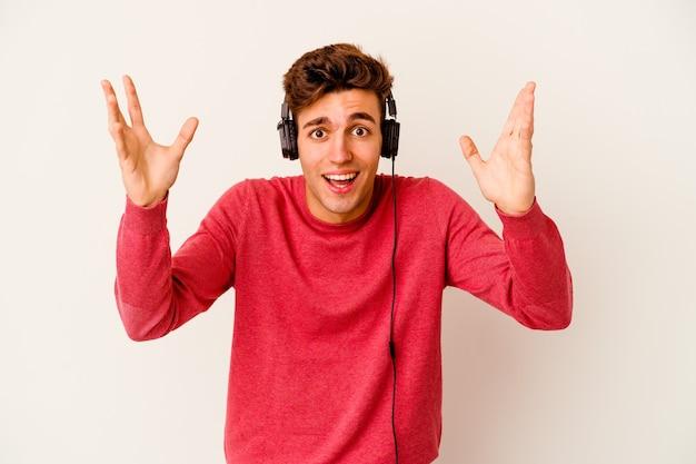 Jovem homem caucasiano ouvindo música isolado