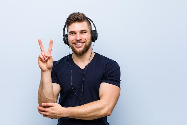 Jovem homem caucasiano ouvindo música, mostrando o número dois com os dedos.