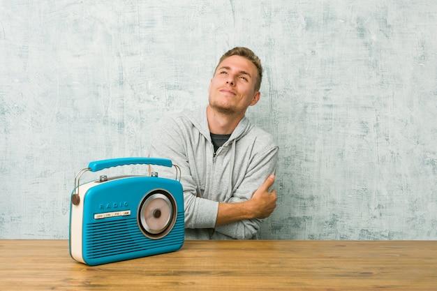 Jovem homem caucasiano ouvindo os abraços de rádio, sorrindo despreocupado e feliz.