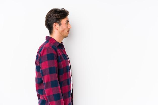 Jovem homem caucasiano posando em rosa isolado olhando para a esquerda, pose de lado.