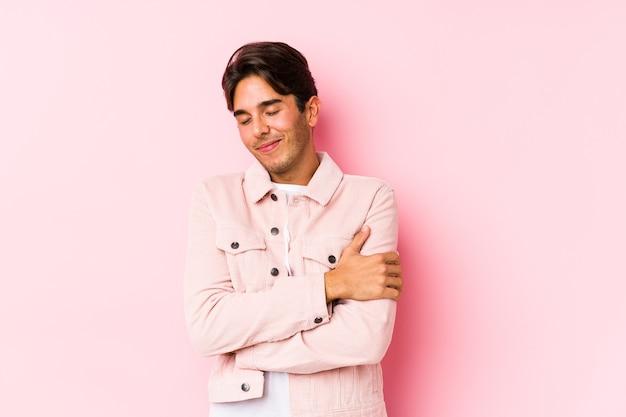 Jovem homem caucasiano posando em um rosa isolado abraços, sorrindo despreocupada e feliz.