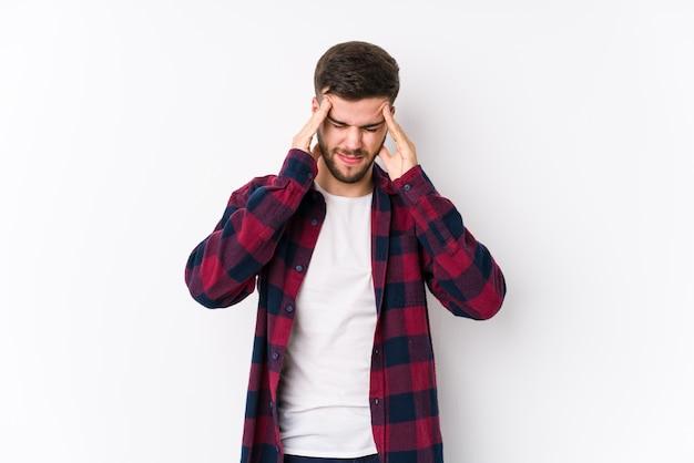 Jovem homem caucasiano posando em uma parede branca isolada tocando templos e tendo dor de cabeça.