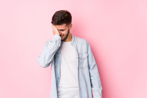 Jovem homem caucasiano posando em uma parede branca, tapa na testa com a palma da mão e fechar os olhos