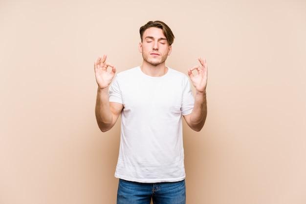 Jovem homem caucasiano posando isolado relaxa após um duro dia de trabalho, ela está realizando ioga.
