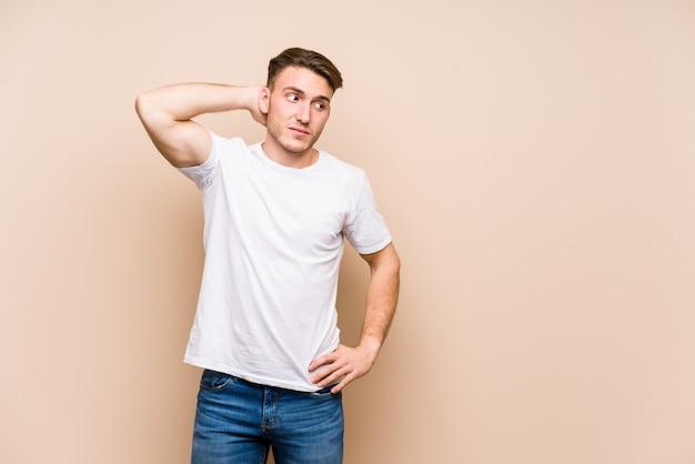 Jovem homem caucasiano posando isolado tocando a parte de trás da cabeça, pensando e fazendo uma escolha.