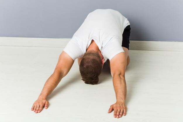 Jovem homem caucasiano praticando ioga de alongamento.