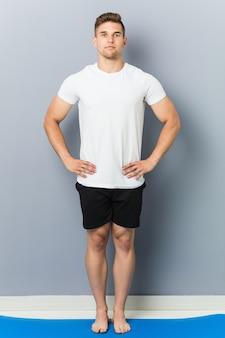 Jovem homem caucasiano praticando ioga interior