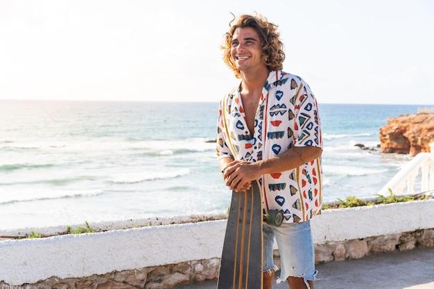 Jovem homem caucasiano praticando longboard na praia