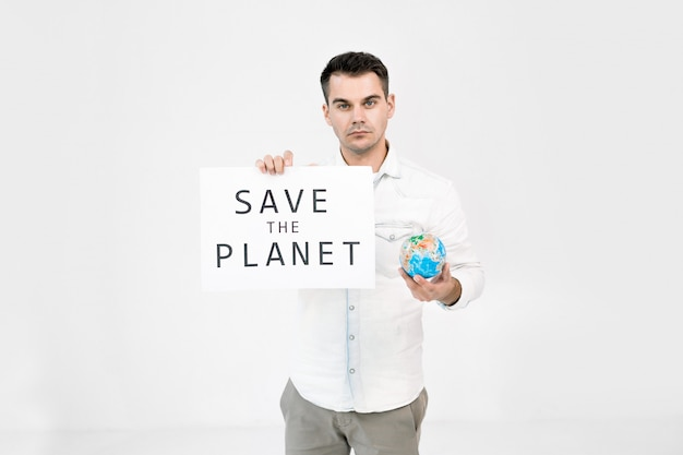 Jovem homem caucasiano, protetor do mundo, voluntário em pé sobre fundo branco e segurando o globo da terra e folha com salvar o texto do planeta.
