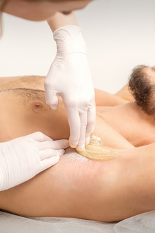 Jovem homem caucasiano, recebendo a depilação da axila em um salão de beleza, depilação masculina nas axilas.
