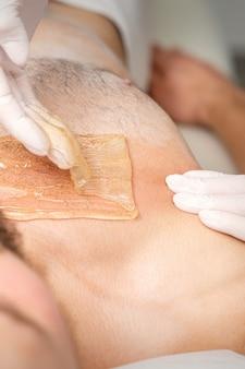 Jovem homem caucasiano, recebendo a depilação do peito em um salão de beleza, depilação do torso masculino.