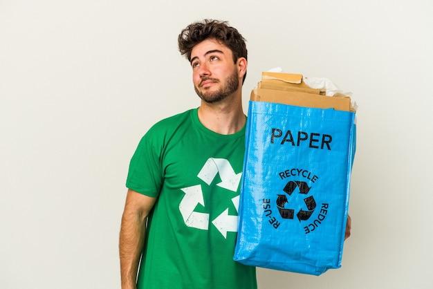 Jovem homem caucasiano reciclando papelão isolado no fundo branco sonhando em alcançar objetivos e propósitos