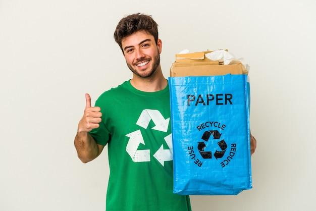Jovem homem caucasiano reciclando papelão isolado no fundo branco, sorrindo e levantando o polegar